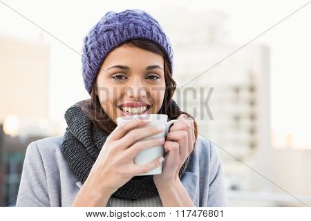 Smiling woman drinking hot beverage outdoor