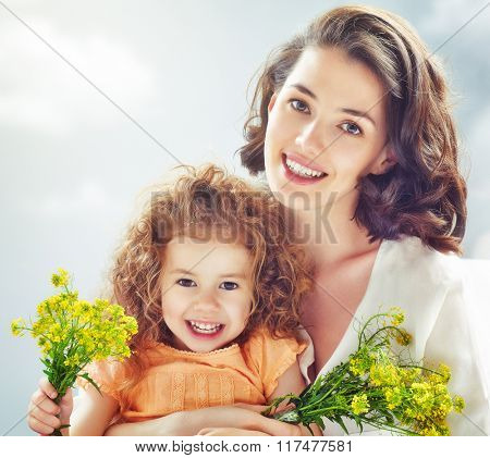Smiling mother and little child. Happy family outdoors