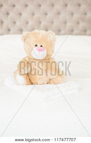 A soft teddy bear on bed