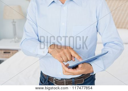 Mid section of man using tablet in bedroom