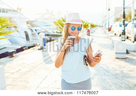 Young Woman Drinking Takeaway Coffee And Walking On The Waterfront In The Morning