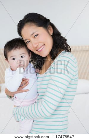 Smiling mother carrying baby daughter in bedroom