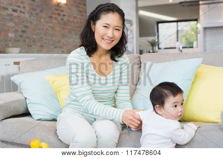 Happy mother with baby daughter in the living room at home
