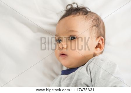 Cute baby on bed at home