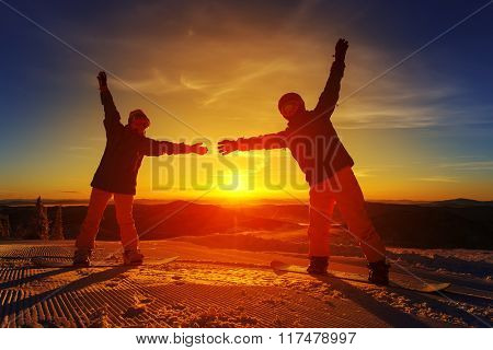 Couple of snowboarders on the mountain with a sunset in the background