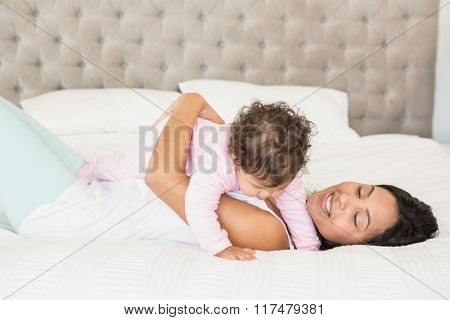 Brunette playing with her baby on the bed