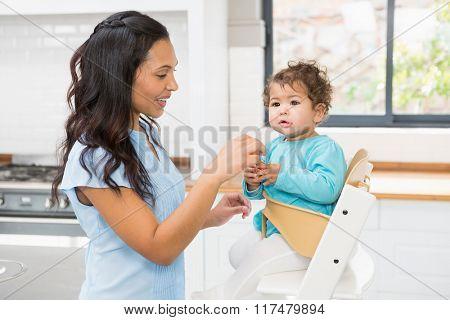 Happy brunette feeding her baby in the kitchen