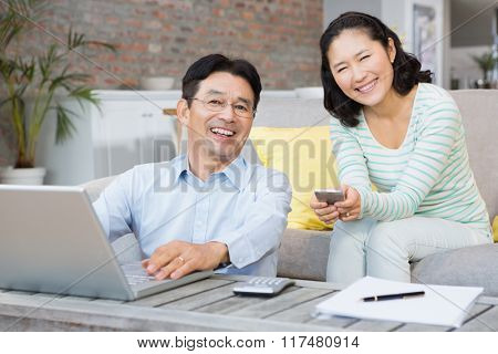 Smiling couple using laptop and smartphone in the living room
