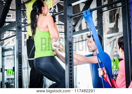 Women and man training in cage for better fitness as group