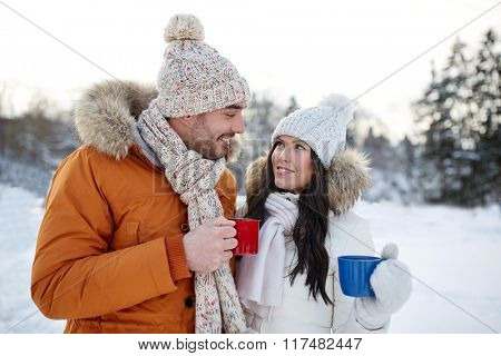 people, season, love, drinks and leisure concept - happy couple holding hot tea cups over winter landscape