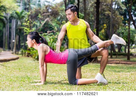 Woman with personal trainer exercising in tropical Asian park gymnastics sport