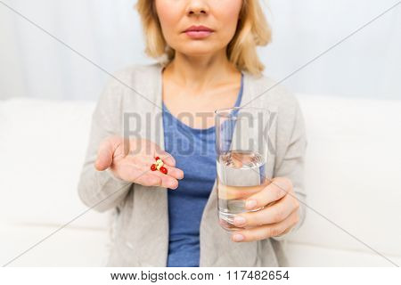 medicine, health care and people concept - close up of middle aged woman with medicine and water glass at home