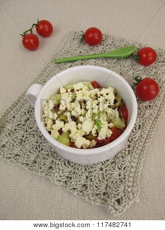 Crumble mug cake with tomatoes, cucumber, olives and feta crumbles