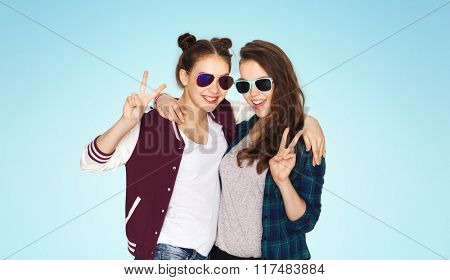 people, friendship, fashion, summer and teens concept - happy smiling pretty teenage girls in sunglasses showing peace hand sign over blue background
