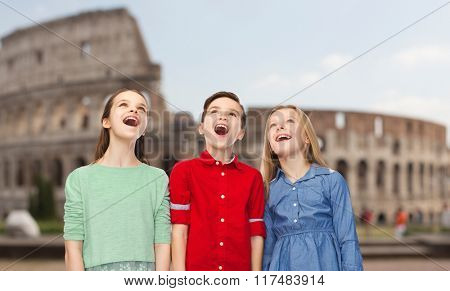 childhood, travel, tourism, emotions and people concept - happy amazed boy and girls looking up with open mouths over coliseum in rome