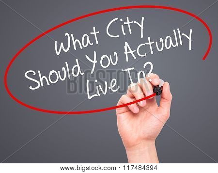 Man Hand Writing What City Should You Actually Live In? With Black Marker On Visual Screen
