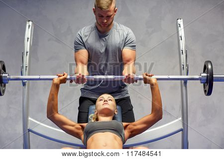 sport, fitness, teamwork, bodybuilding and people concept - young woman and personal trainer with barbell flexing muscles in gym