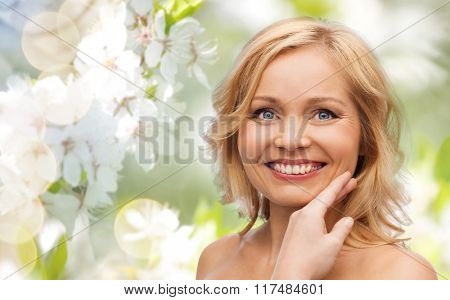 beauty, spring, skincare and natural cosmetics concept - smiling woman with bare shoulders touching face over cherry blossom background