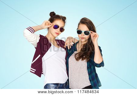 people, friendship, fashion, summer and teens concept - happy smiling pretty teenage girls in sunglasses over blue background