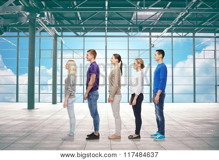 travel, vacation and people concept - group of men and women from side over airport terminal window and sky background