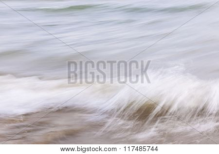 Ocean waves crashing on sandy beach abstract background, in-camera motion blur.