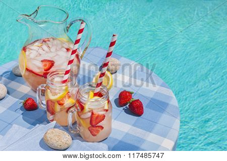 Ice cold homemade strawberry lemonade in jug and glasses with paper straws on outdoor pool side table in summer with copy space