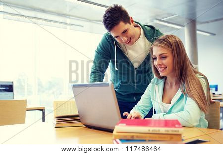 people, education, technology and school concept - happy students with laptop computer networking in library