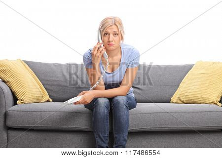 Sad young girl talking on telephone seated on a gray sofa and looking at the camera isolated on white background