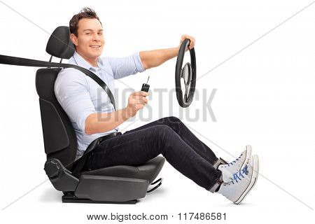 Young man sitting on a car seat and holding a steering wheel and a car key isolated on white background