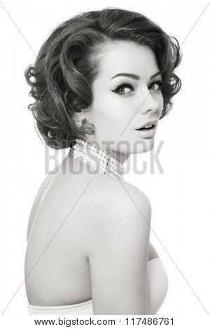Black and white shot of young beautiful smiling sexy woman with winged eyes make-up and curly hairstyle over white background