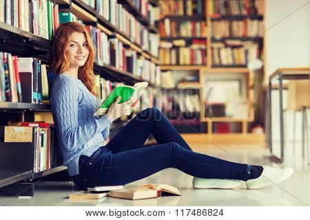 people, knowledge, education and school concept - happy student girl sitting on floor and reading book in library