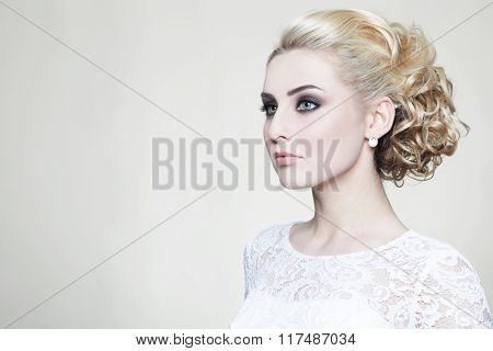 Young beautiful blonde bride with stylish prom hairdo and make-up
