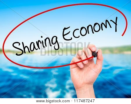 Man Hand Writing Sharing Economy With Black Marker On Visual Screen