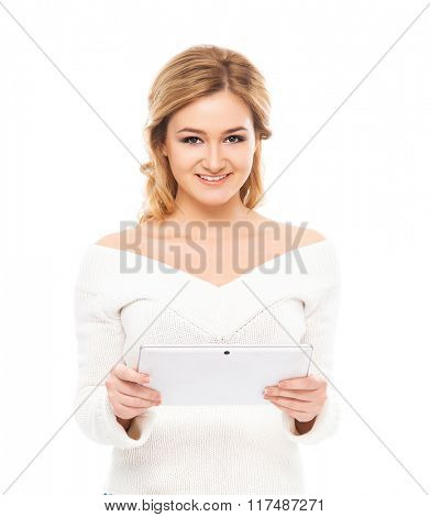 Young and beautiful teenager girl holding a tablet pc in her arms isolated on white