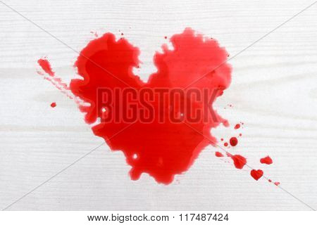 Heart Shaped Drops Of Red Juice Against Wooden Background