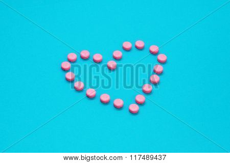 Pink Pills In Heart Shape  On Blue Background