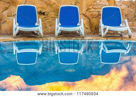 Sunloungers near swimming pool and reflected their in blue water