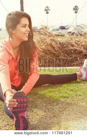 Young sportswoman stretching.