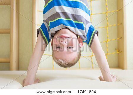 Boy Standing Upside Down In Gym Class.