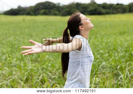 side view of smiling teen girl with arms open on grassland