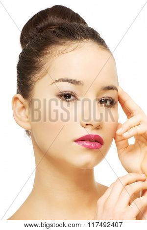 Woman with full make up touching face.
