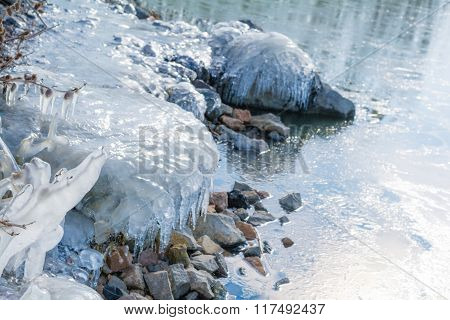 Frozen rocks with ice in the winter lake