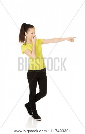 Young shocked woman pointing aside.