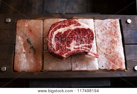 Bone In Rib Eye Row Steak On Pieces Of Salt