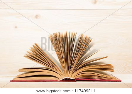 Open book on wooden table. Back to school. Copy space