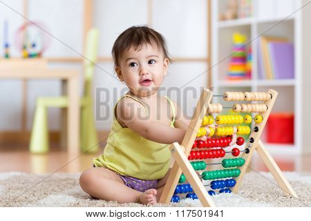 child girl playing with counter toy at nursery