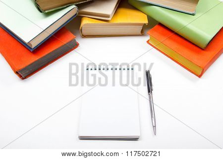 Stack of colorful books, notebook with blank sheet paper and pen on wooden table. Back to school. Co