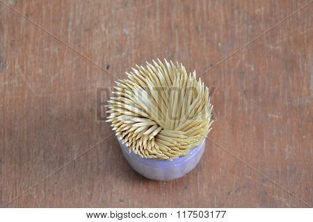 toothpick in plastic box packaging on wooden board