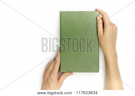 Hands hold blank green hardcover book on white background.