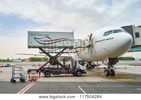 DUBAI, UAE - JUNE 23, 2015: Boeing 777-300ER docked in Dubai airport. Dubai International Airport is a major airline hub in the Middle East, and is the main airport of Dubai.